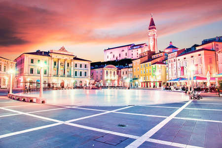 Beautiful amazing city scenery in the central square with the old clock tower in Piran, the tourist center of Slovenia in the light of lanterns. popular tourist attraction. Wonderful exciting places. (vacation, rest - concept)