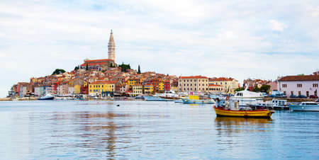 Beautiful city landscape with sea boats, colorful houses and an ancient tower in Rovinj, Croatia. popular tourist attraction. (vacation, rest - concept) Stok Fotoğraf
