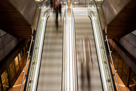 Abstract image with silhouettes of people on the subway escalator (hurry, rhythm of life, time flow - concept)