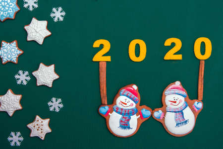charming atmospheric Christmas background with festive biscuits in the form of snowflakes and snowmen as a symbol of the new year 2019 (greeting card, greetings - concept)