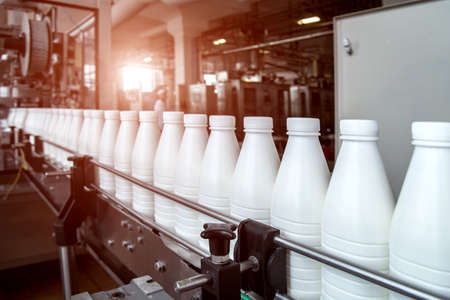 White plastic milk bottles on the conveyor on a modern dairy plant