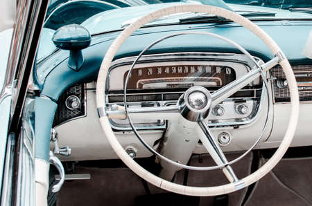 Fragment of interior retro car with speedometer, toggle switches and steering. vintage style