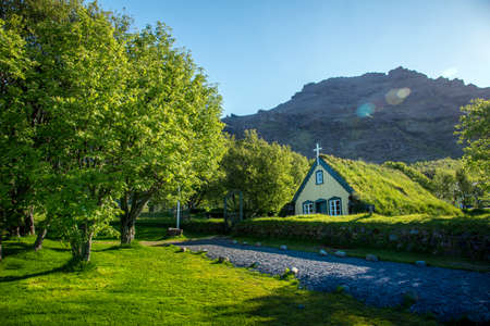 Charming mystical scene with turf roof church in old Iceland traditional style and mystical cemetery in Hof, Skaftafell, Vatnajokull National Park. Exotic countries.
