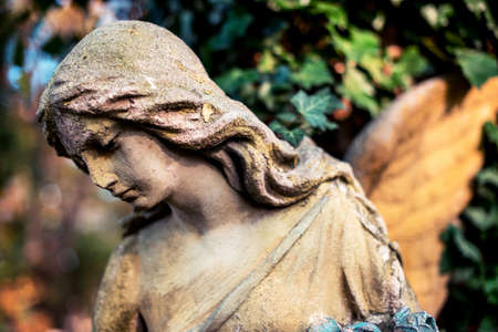 A fragment of ancient sculpture angel in the old cemetery. Symbol of love, invisible forces, purity, enlightenment, ministry, salvation. Chariot. Standard-Bild