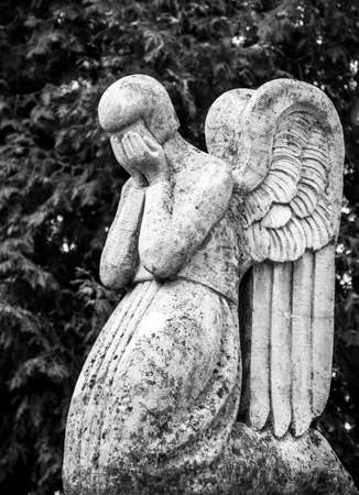 An abstract image of a sad angel who mourns the loss with his hands in his crying eyes. Standard-Bild