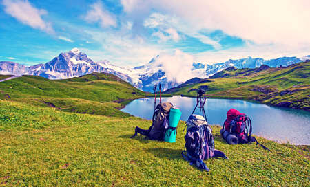 Backpacks, trekking pole and camera on a tripod in the mountains in the Swiss Alps, Europe (still life coach, company, friendship, background - concept)