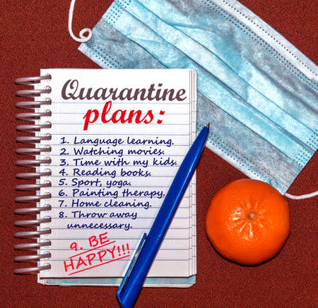An abstract image of a medical mask and a notebook with plans for what to do while a coronavirus quarantin.Emphasis on the