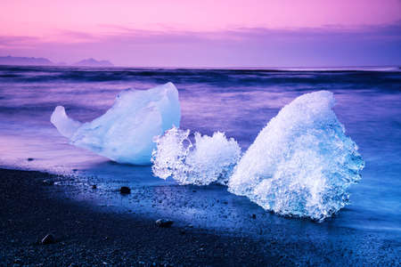 magical charming beautiful landscape with a piece of ice like a sculpture on the Diamond beach near glacier lagoon Jokulsarlon, Iceland at dawn. Exotic countries. Amazing places. Standard-Bild