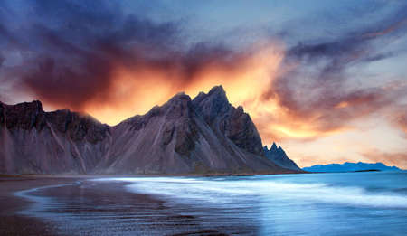 Scenic landscape with most breathtaking mountains Vestrahorn on the Stokksnes peninsula with the waves of the bay at sunset in Iceland. Exotic countries. Amazing places.