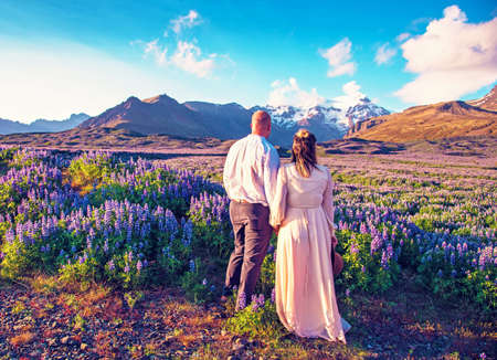 Beautiful landscape with oung couple in lupine flowers on a background of mountains in Iceland. Magical places. Exotic countries.