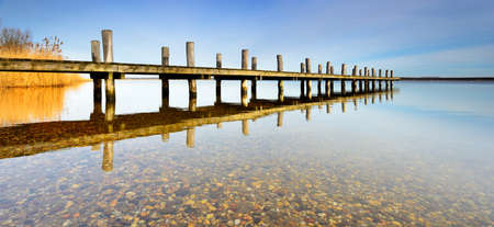 Calm clear lake with wooden pier