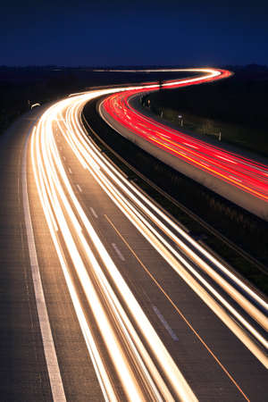 Winding Motorway at night, long exposure of headlights and taillights in blurred motion