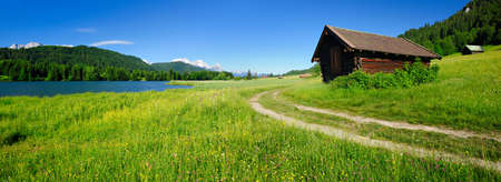 Footpath through Bavarian mountains with mountain lake and barns, Mount Zugspitze behind