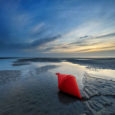 Low Tide Seascape with Buoy at Tidal Pool at Sunset, St. Peter Ording, Germany Stock Photo