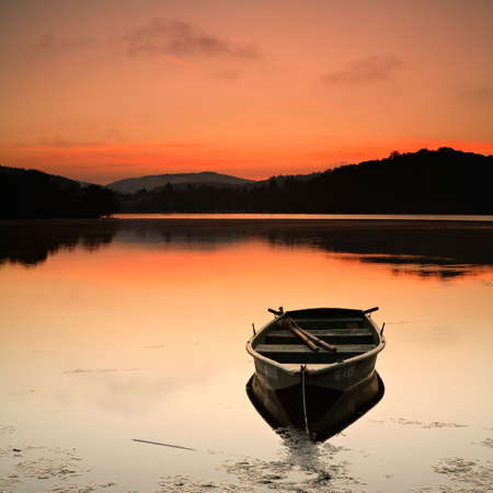 Fishing Boat on a Calm Lake at Sunrise Фото со стока