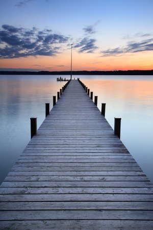 夕暮れ時、長い木製の桟橋が湖
