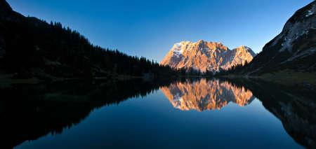vastness: Alpenglow on Mount Zugspitze reflecting in mountain lake