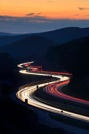 Lange blootstelling aan auto lichten op de snelweg die door heuvels bij zonsondergang kronkelt Stockfoto