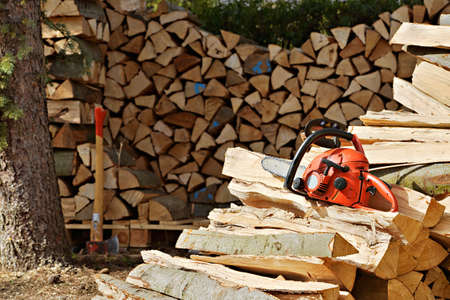 Pile of Lumber, Chainsaw and Splitting Ax