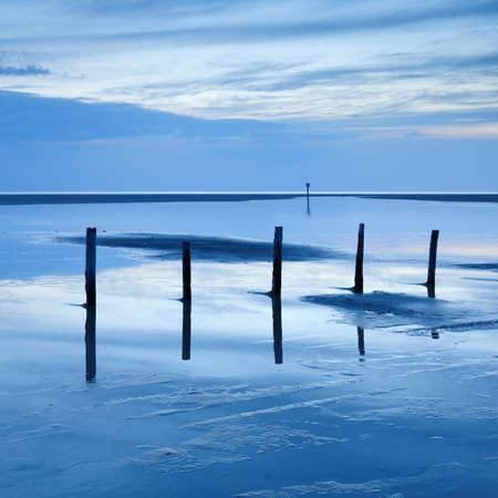 Low Tide Seascape with Wooden Posts in Tidal Pool at Sunset, St. Peter Ording, Germany
