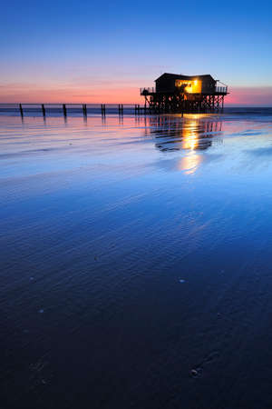 Stilt house and Jetty on the beach at sunset, St. Peter Ording, Germany