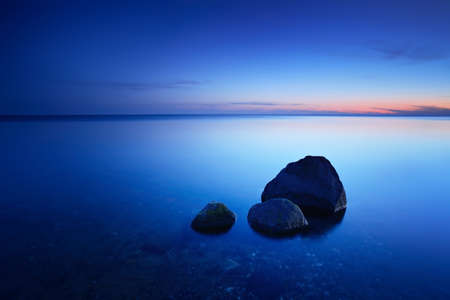 After Sunset, Boulders in the Calm Sea, Baltic Sea, Rugen Island, Germany Stock Photo