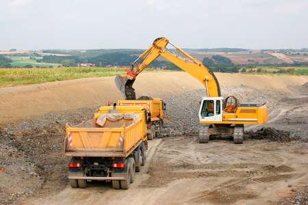 Motorway under Construction, Excavator and Dump trucks at Work Foto de archivo