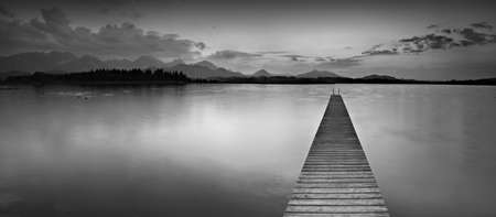 Long Wooden Pier into Lake Hopfensee in the Bavarian Alps, Black and White Фото со стока