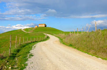 Winding Dirt Road Leading to a Typical Farmhouse on Top of a Hill, Tuscany, Italy