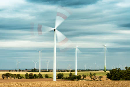 Wind Turbines in Wheat Field Under Stormy Sky, Blades intentionally blurred by rotation