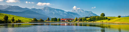 Panoramic bavarian landscape with small village by a lake, the alps behind, Allgau, Bavaria, Germany