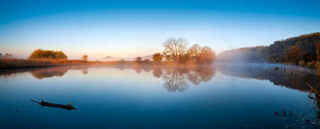 Calm Lake in Autumn at sunrise, fog rising from the water, blue sky