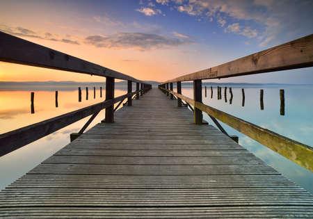 Lake with Long Wooden Pier at Sunrise 免版税图像