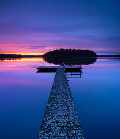 Wooden pier in calm lake covered by fall leaves in autumn after sunset Stock Photo
