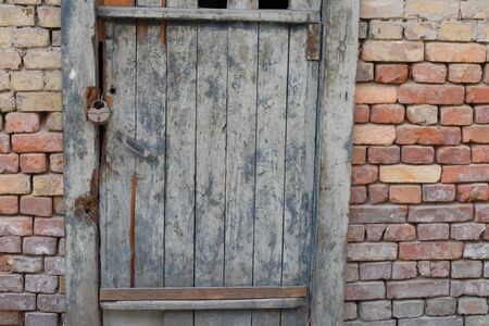 decrepit: Decrepit and old door and brick wall in the evening