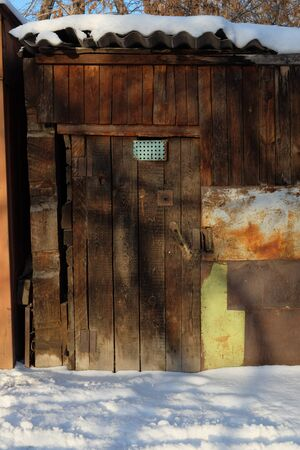 barns winter: Old wooden door of a barn with shadows from the branches of the tree