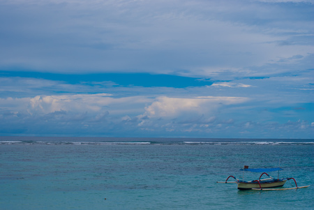 shallop: Lonely boat on the sea in Bali in cloudy weather.