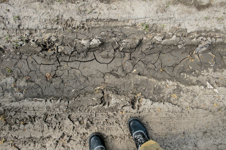 adult footprint: Top view on mud in rural road track and boots. Stock Photo