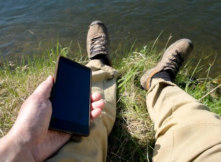 uses: Man uses smartphone mobile sitting on the river shore Stock Photo