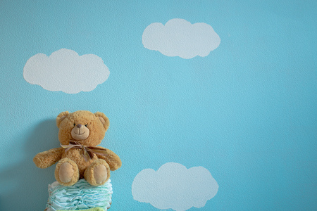The toy is sitting on the diapers in the wall background of blue sky and clouds Stock Photo