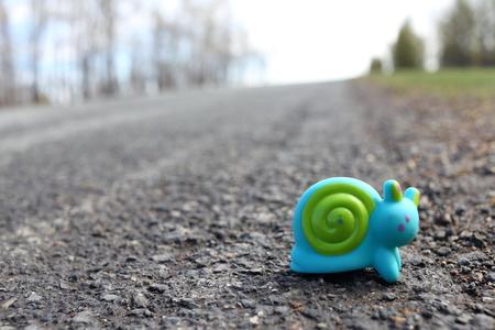 Caracol de juguete en la carretera Foto de archivo - 77932547