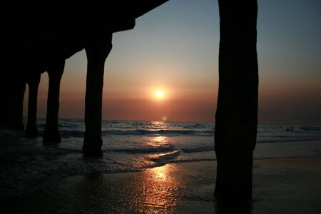 evocative: Silhouette of pier at sunset as waves playfully fall to shore Stock Photo