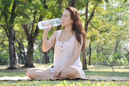Girl is Drinking water at park photo