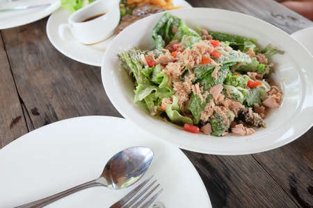 side salad: Tuna salad on white dish and wooden floor.