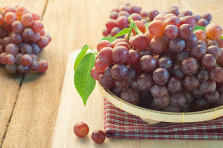 wooden floors: Grapes on bamboo basket and wooden floors. Stock Photo