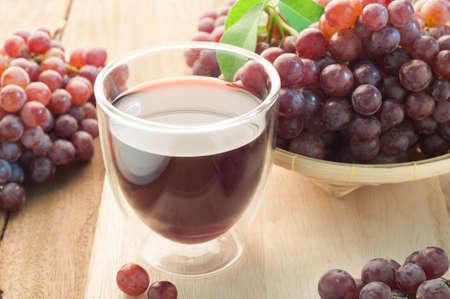 wooden floors: Grape juice and group of Grapes on bamboo basket and Wooden Floors.