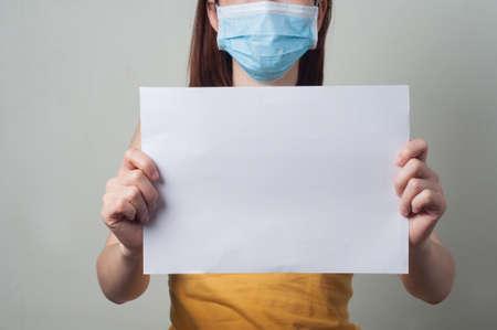 pacjent: Azji Kobiety są pacjenci nosić maskę trzyma pusty papier. Zdjęcie Seryjne