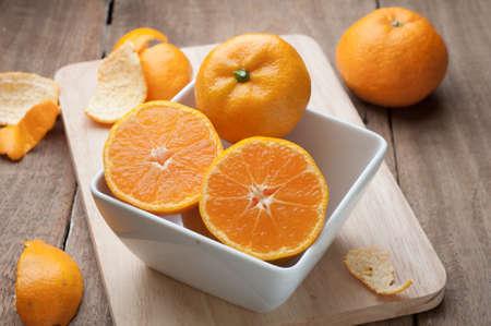 wooden floors: Group of orange fruit on white plate and wooden floors. Stock Photo