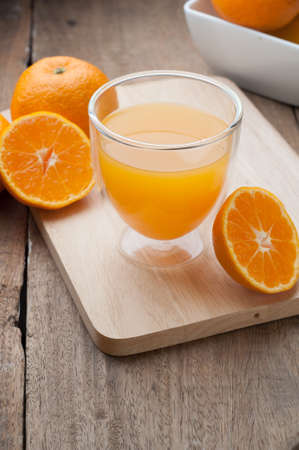 wooden floors: Glass of orange juice on wooden cutting boards and wooden floors. Stock Photo