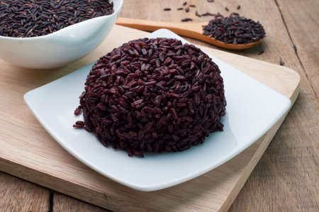 Black Rice cooked on white plate and black rice grains organic. View from above rice cooked.